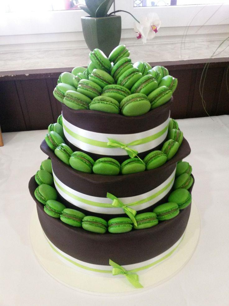 Třípatrový svatební dort obalený čokoládovou potahovací hmotou z belgické čokolády, dozdobený saténovými stuhami a spoustou pistáciových makronek.
