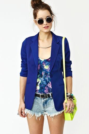 Blazer Azul eléctrico, Blusa floreada, Short Jean desgastado, Cartera verde neon, cinturón y gafas redondas. Nasty Gal