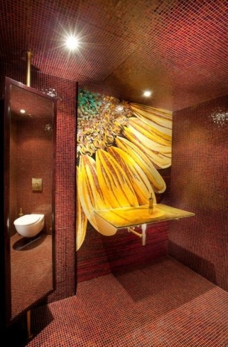 a closeup of a sunflower is the focal point of this powder room. The fact that the walls, ceiling and floor are all covered in the same tile makes the sunflower stand out even more.