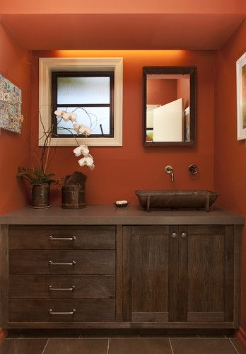 This bathroom has so many great details. Orange walls bring out the deep colors in the woodwork and salvage sink. White moulding around the square window highlights the window's quirky size. ~s