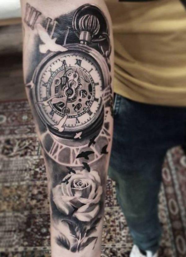 Unterarm Tattoo für Männer mit einer römischen alten Uhr. Drum herum befinden sich mehrere weiße und schwarze Vögel (Vogelart: Taube) die fliegen. Die schöne große Reise verleiht der Tätowierung etwas ganz Besonderes.