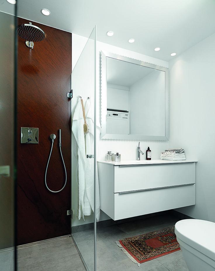 Chefkonditor Lars Juul-Mortensen har med et simpelt greb skabt en varm atmosfære i sit stilrene badeværelse. Bruserummet er bygget op af rustne jernplader, der står i rustik kontrast til de enkle hvide skuffer og det lyse stengulv. Pladerne er specialfremstillet og lakeret, så de tåler vand og rengøring.