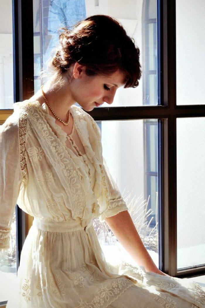 unique wedding dresses, woman with tied back dark hair, sitting near a window and looking down in profile, wearing a pearl necklace and a vintage cream Victorian era wedding dress with lace and embroidery