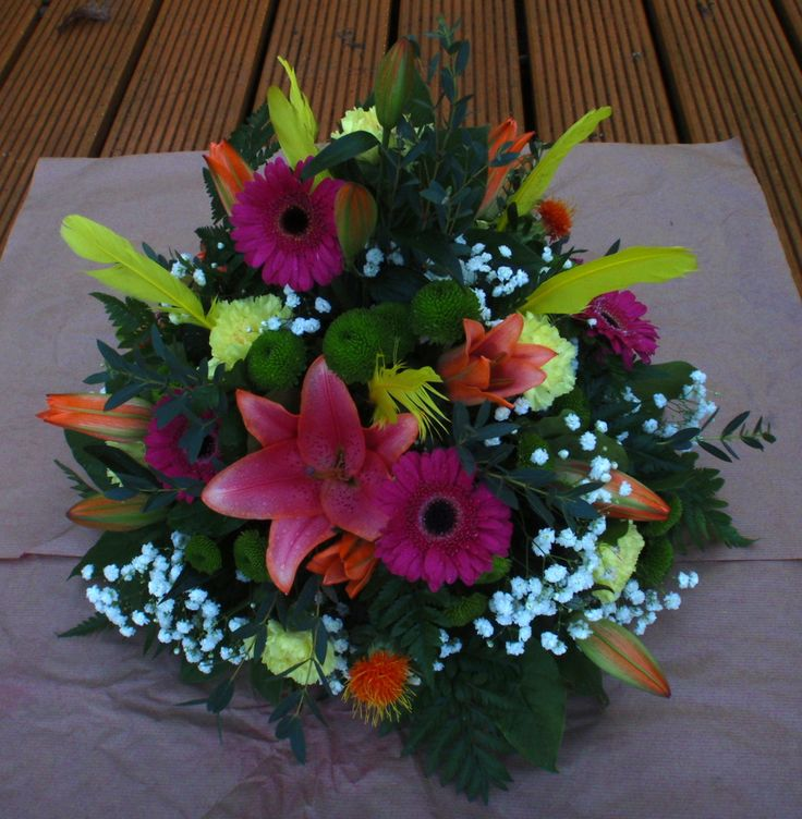 A Copacabana posy made up of tropical colour flowers with yellow feathers.