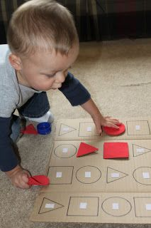 DIY shape puzzle made with a pack of colored foam paper, leftover velcro, and a cardboard box.