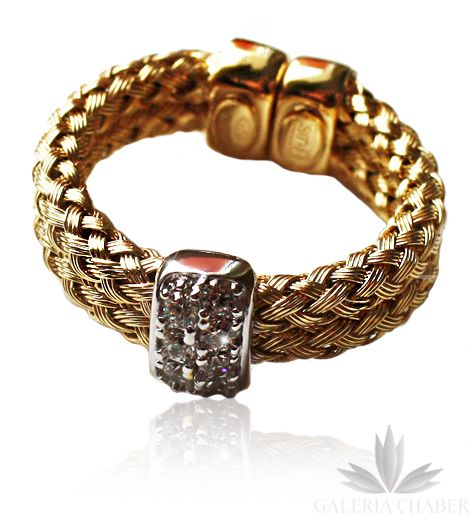 Ciekawy pierścionek wykonany ze srebra próby 925, w kolorze złotym. Wyrób rodowany. Pierścionek regulowany, minimalny rozmiar to 15. Możliwe jest rozciągnięcie pierścionka dzięki pęknięciu. Splot obrączki to dwa klasyczne warkocze połączone ze sobą, ozdobione na środku wstawką w kolorze srebra wysadzaną Cyrkoniami w kolorze białym. Obrączką o szerokości około 0,5 cm.   Szczególnie polecamy inne wyroby utrzymane w podobnej stylistyce, pierścionki oraz bransoletki plecione, wykonane ze…
