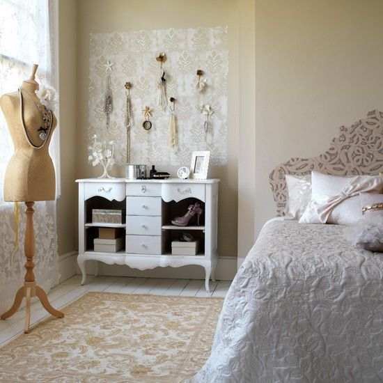 Vintage-style bedroom with brass hooks and wall stencil