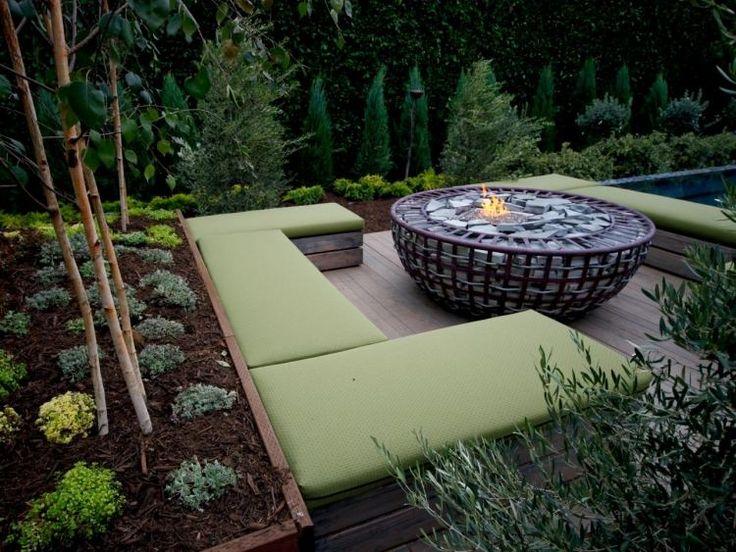 Sitzecke mit Feuerstelle im Garten von Zypressen umgeben