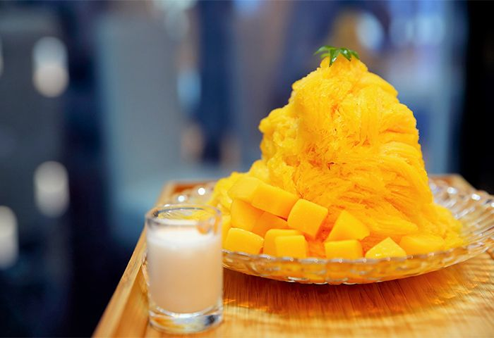 Mango Bingsu Patbingsu is a popular Korean shaved ice dessert with sweet toppings that may include chopped fruit, condensed milk, fruit syrup, and red beans. Varieties with ingredients other than red beans are called bingsu.
