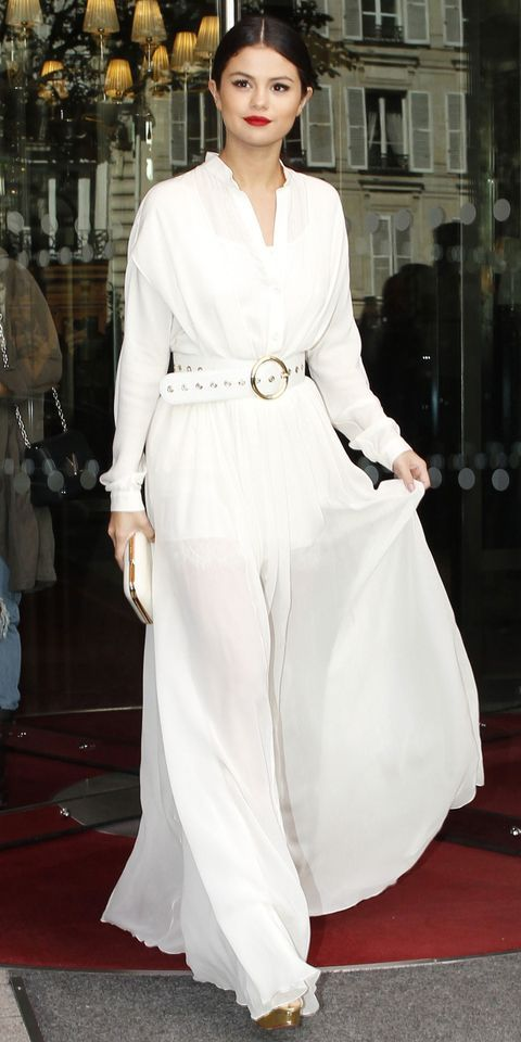 Selena Gomez in a white long-sleeve blouse tucked into belted ground-grazing skirt, both by Elie Saab.