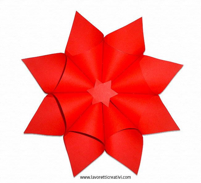 Stella di Natale realizzata con il cartoncino di colore rosso. La decorazione legata con un filo può essere appesa al soffitto dell'aula di scuola o di ca