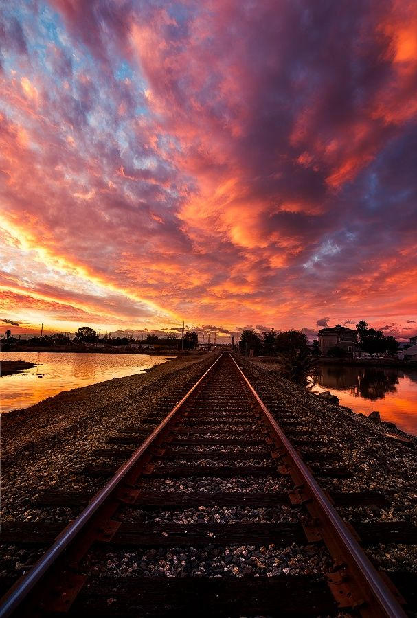 Fiery #sunset, orange and purple clouds ahead on the #railroad #tracks, with water reflections off the lake on both sides. SKY LIGHTS.