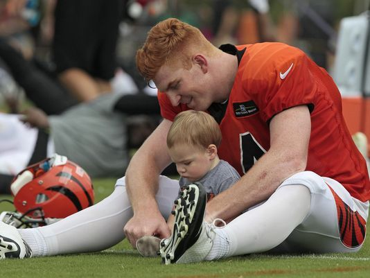 Walkthrough: Bengals deleted scenes. Photo: Cincinnati Bengals quarterback Andy Dalton (14) stretch with his son Noah, 13 months, on the field after practice at the Bengals training facility next to Paul Brown Stadium in downtown Cincinnati on Monday, Aug. 17, 2015. The Enquirer/Sam Greene