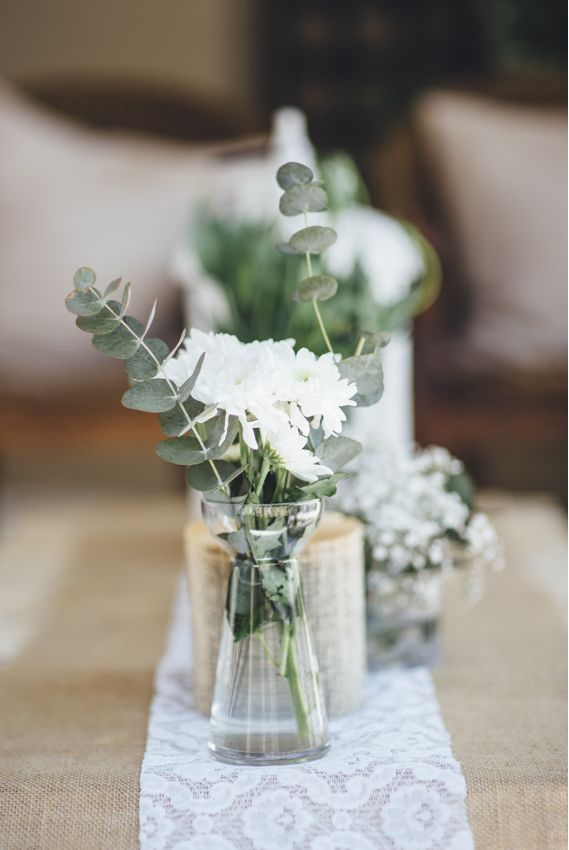 Hochzeit – Simple rustic arrangement of chrysanthemums and eucalyptus in glass vases and bo
