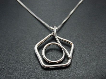 Necklace with pendant in the shape of a pentagon. Electroformed copper, silver plating and rhodium.