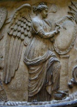 Particolare dalla Colonna Traiana, l'immagine della Vittoria, intenta a scrivere le imprese di Traiano su uno scudo,si trova circa a metà della colonna e separa la prima campagna (parte più in basso) dalla seconda