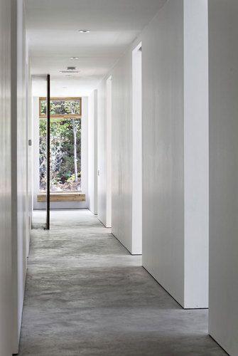 Witte strakke muren zonder plinten voor een strak geheel. Met betonnen vloer.
