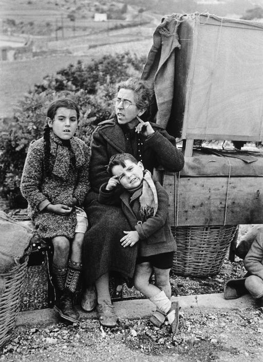 Robert Capa ESPAÑA. 15 de enero de 1939. En la carretera de Tarragona a Barcelona. La gente de Tarragona que buscan refugio en Barcelona, antes de la evacuación de la ciudad. Muchos de ellos murieron o perdieron sus pertenencias durante los ataques aéreos fascistas.