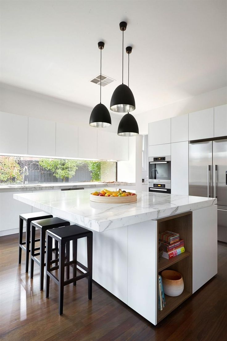 elegant meals area in the kitchen, supplemented by square island bench, three black stools, and three black pendant lights