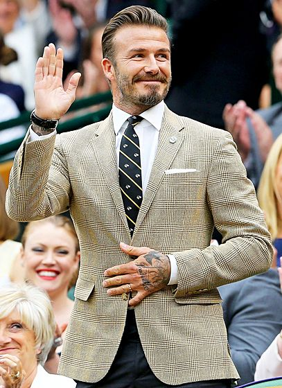 David Beckham waved in the stands as he watched some tennis at Wimbledon in London.