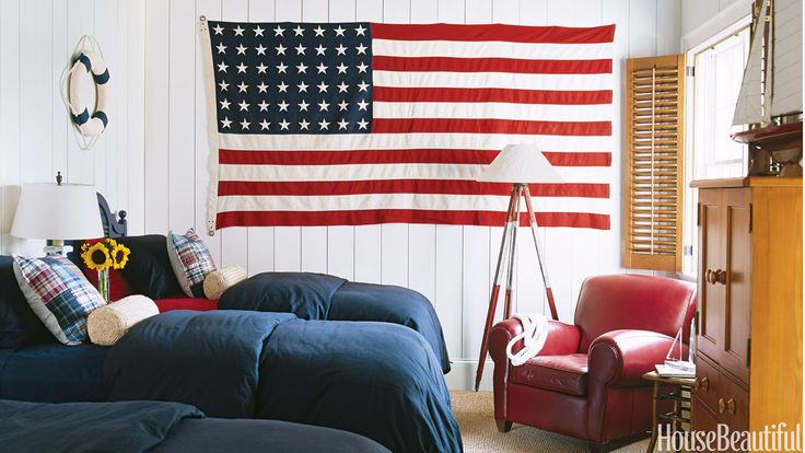 Suzanne Kasler decorated this bedroom on Lake Thurmond, South Carolina with nautical elements and an oversize American flag.   - HouseBeautiful.com