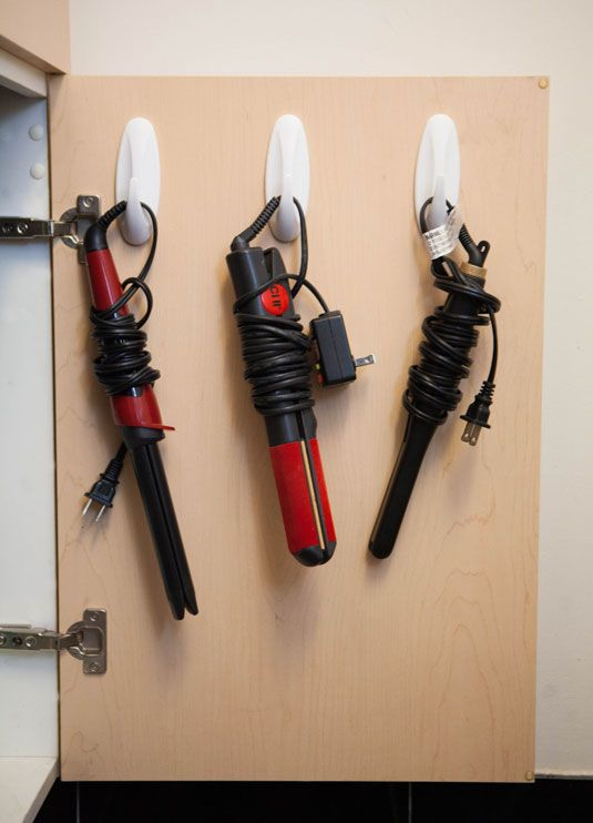 You can use hooks inside of a cabinet door for lots of things! Putting your hair tools there is just one of the many ideas. When you put them inside a drawer, they always get too messy, and this way everything looks neat! | Organization Tips |