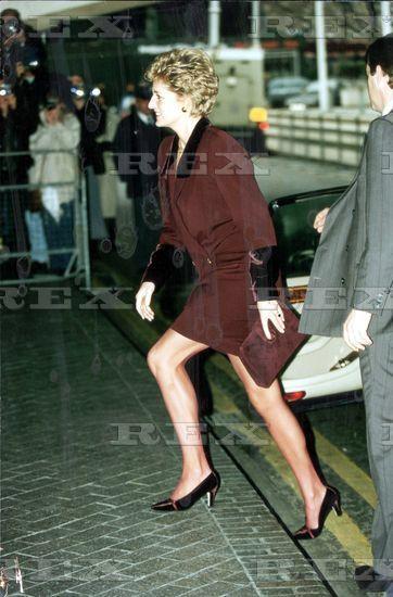 1993: Diana Princess of Wales - wearing a tan/brown suit with contrast black upper lapels, a matching clutch bag, brown court shoes, really short skirt - just exited a car. Her PPO on the right, partially visible.