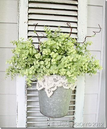 Hang a bucket full of flowering plants on an old shutter