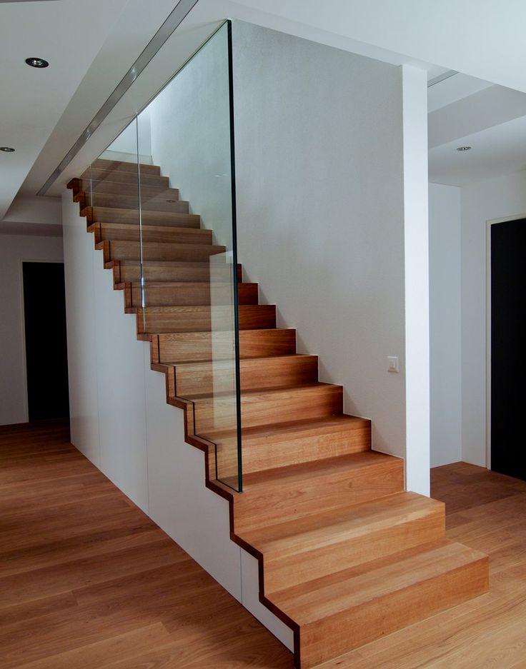 Stufen und Futterbretter in Eiche natur geölt als Faltwerk ausgebildet und auf zwei Holzsattel befestigt. Glas unten in Stufen und Futterbretter eingenutet und oben in Metallkonstruktion geklemmt. Die Wand hat keine tragende Funktion.