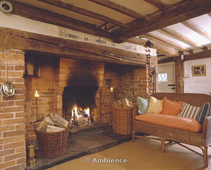 Baskets of logs in inglenook fireplace in beamed cottage living room with wicker sofa and sisal carpet