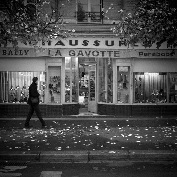 Passant sur le trottoir devant un magasin de chaussure