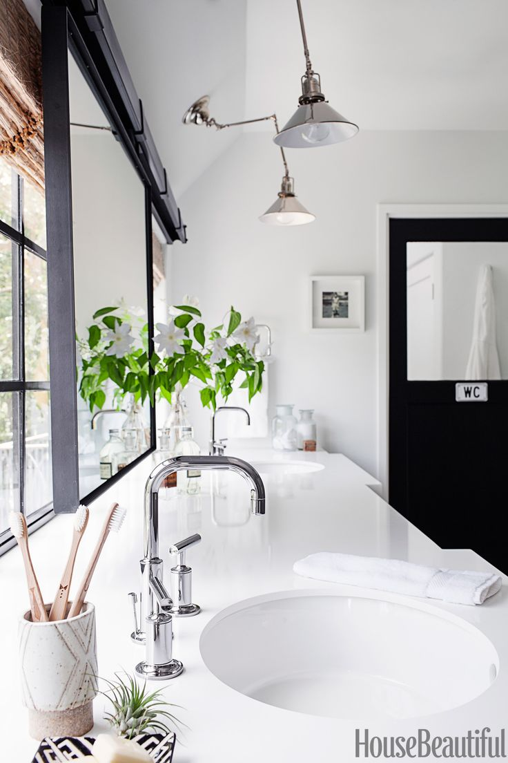 """Designer Kim Lewis liked the clean geometric lines of the Purist faucet and used it with two Verticyl sinks, all by Kohler. They're set into a vanity topped with Silestone in Yukon Blanco, """"a great material that's virtually bulletproof,"""" she says. In order to make the exceptionally long vanity feel more like a piece of furniture, the front of it jogs in and out. Barn-door hardware for the mirror from Rustica Hardware. Reed Industrial swing-arm lights from Rejuvenation. Plus: 6 Decorating ..."""