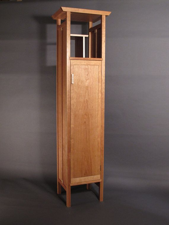 This tall and narrow mid century modern cabinet utilizes smart vertical space for a beautiful storage option with a small footprint. Our Cherry tall armoire cabinet can be used as a freestanding linen closet or as a stately bar, displaying bottles and decanters, containing fine glassware and cigars. As a bedroom armoire or large nightstand you can store sweaters and jewelry, display photos and fine art. -A defining piece of Mokuzai Furnitures fine craftsmanship. -Signature book-matched…