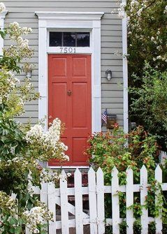 I've always been obsessed with having a house painted grey, white trim, and a red door -- and this even has a white picket fence!