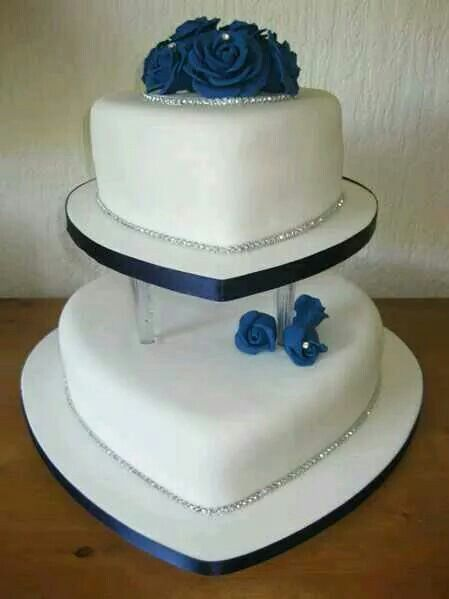 2 layered cake with blue roses on top and silver linen at the bottom