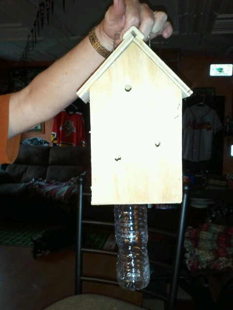 This is a carpenter bee catcher they will go in the holes (on all sides) and go toward the light and go in the bottle and can't get out, and die. I glued the bottle cap in a hole in the bottom. So when the ARE DEAD, you can unscrew it and dump them in the garbage. Or unscrew it put another cap on it and freeze or through away. This is a standard bird house, no doors or windows. I drilled 5/8 in holes on all sides. It works!!!