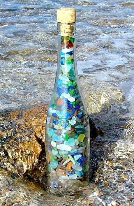 Decorative Bottle Idea: Fill a clear glass bottle with seaglass..., pebbles, and/or small shells from the beach: http://www.completely-coastal.com/2014/11/decorating-ideas-with-bottles.html