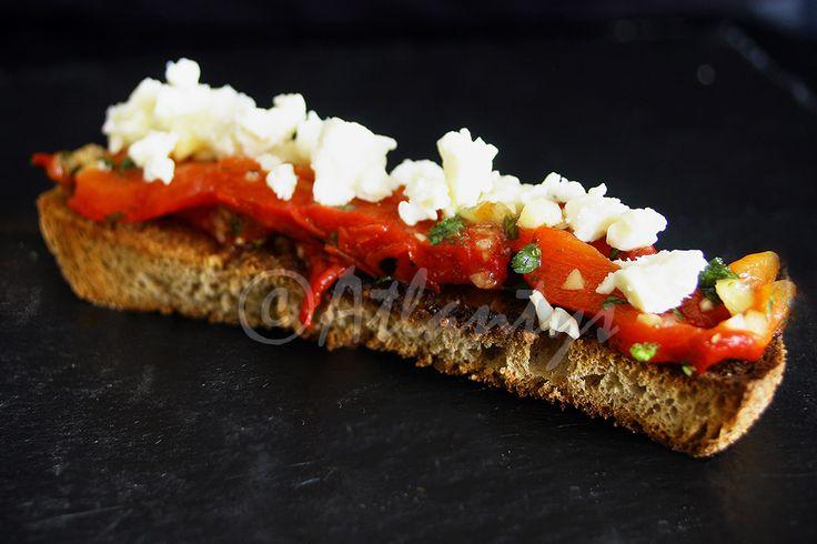 Ingredientes   Pimentos grelhados e temperados (exemplo de como fazer aqui )   Pão rústico cortado em fatias   Queijo feta   Coentros fr...