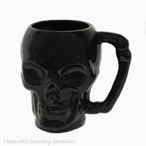 This black skull mug or coffee cup with a creepy bone style handle is finished in a shiny black glaze. This black skull mug is a new addition to my collection of skulls I make. This skull mug is made to be used, the inside is also glazed in a food safe black glaze giving it a totally creepy macabre look. This skull is made to order and ships in approximately 2 - 4 weeks. This skull mug is made with ceramic slip using a plaster mold for uniformity. Each piece is kiln fired and hand brushed...