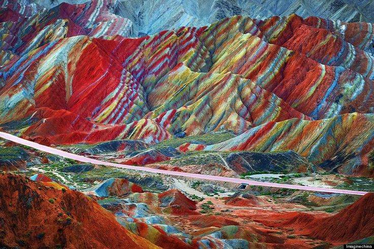 The mountains are part of the Zhangye Danxia Landform Geological Park in China. Layers of different colored sandstone and minerals were pressed together over 24 million years and then buckled up by tectonic plates. Photographer unknown.