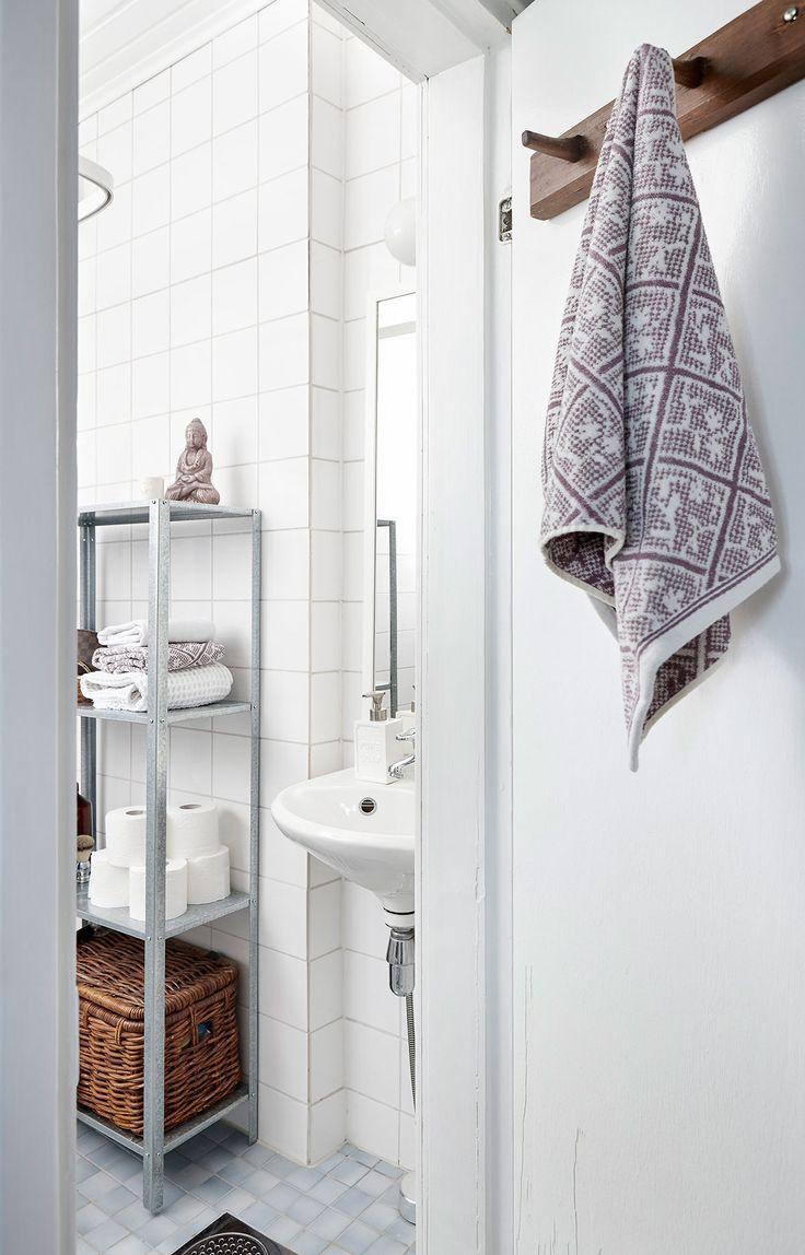 Kylpyhuone uusittiin putkiremontin yhteydessä muutama vuosi sitten, mutta Niina ja Ossi viimeistelivät maalaamalla katon ja oven valkoisiksi. Metallihyllykkö on Ikeasta ja kuviolliset pyyhkeet pariskunta toi Espanjasta.
