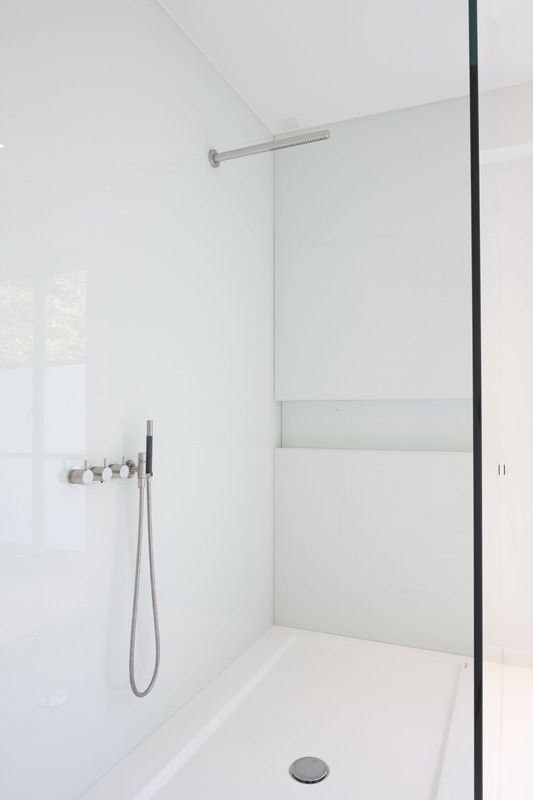 White ?solid surface? and white glass shower with built in shelve and Vola shower head and taps. Designer unnkown.