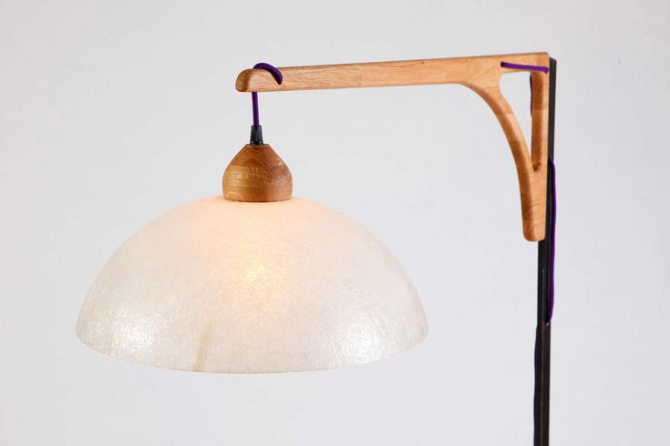 Li.Mod.Cra.F Floor lamp with steel base and wooden arm. The color cable is knitted through the oak arm. Different lamp shades to choose from.
