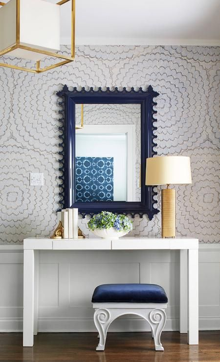 Illuminated by a brass Caged Lantern with Paper Shade a West Elm Parsons Desk with Drawers sits against a wainscoted wall above a blue velvet bench and beneath a navy blue scalloped mirror mounted on gray floral wallpapered walls and illuminated by a gold table lamp complementing gold book ends in this beautiful navy blue and gold foyer.