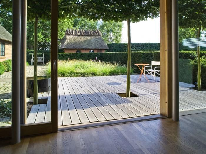 """The house opens onto a deck-as-outdoor-room, where """"walls"""" are defined by a high, close-clipped hedge; the geometric severity is softened—in typical Oudolf fashion—by a sprawl of grasses."""