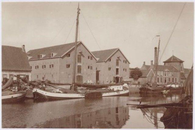 De twee pakhuizen van Gerritsen aan de Kleine Koppel 11 en 12. Rechts daarvan de Eemstraat, vóór 1912 Wolfertsteeg geheten. Vervolgens het kantoor van J.L. van Nieuwenhuizen, graanhandelaar. De onderste helft van molen De Rijzende Zon (nr. 14) werd door hem als graanpakhuis gebruikt.