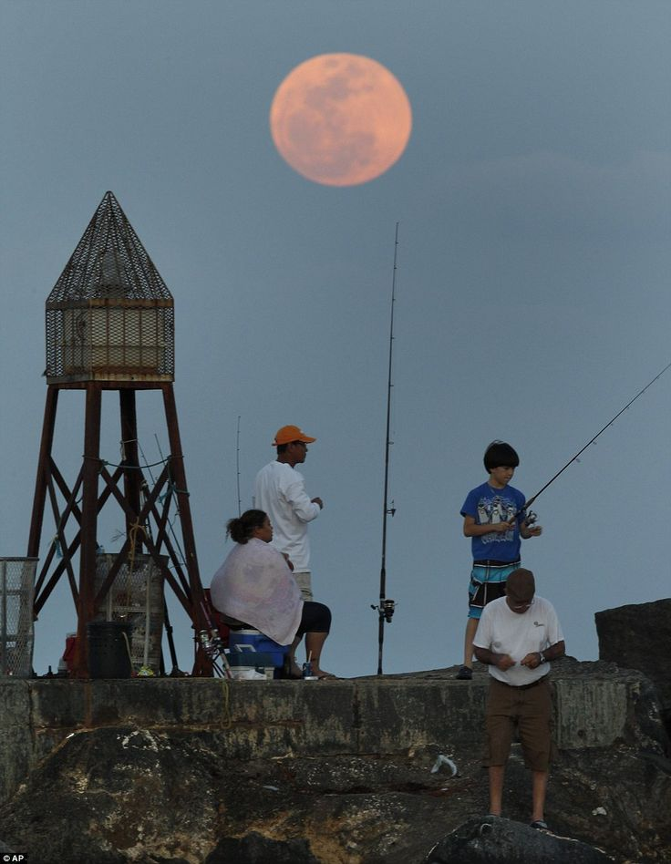 *May, 2012...Fishermen near Bal Harbour in Florida rest on a jetty as the supermoon rises in the Atlantic Ocean