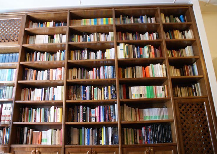 Una libreria in legno di noce realizzata a Roma, nella casa di due docenti universitari che avevano la necessità di riporre una grande quantità di libri.