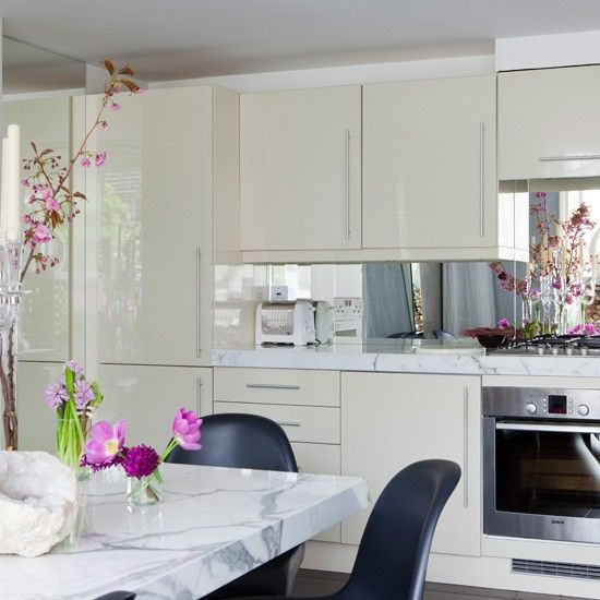 A fresh decorating idea is using light-reflecting surfaces - such as lacquered kitchen cabinets and mirrored splashbacks - for a light, bright kitchen. A marble table, with moulded black dining chairs, provides the space with a luxurious finish.