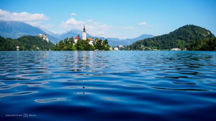 Meer van Bled (Slovenië). Uitzicht op het eilandje met de 'Maria Hemelvaartskerk' en links achter het 'Kasteel van Bled' by Jacintha Bol